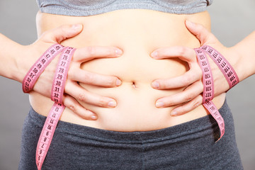 Woman touching stomach holding measuring tape
