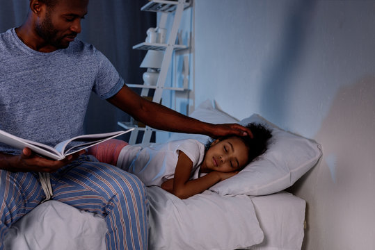african american father holding book and palming sleeping daughter at home