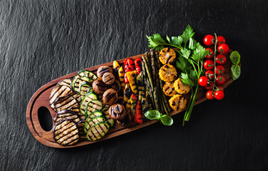 food background of vegetables on the grill . healthy summer food on black shale