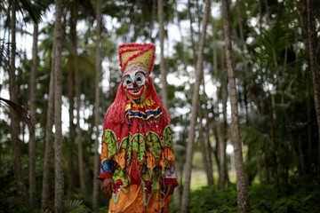 """A member of the """"Bloco Ultima Hora"""" group poses for photo during Carnival of the Waters, where costumed and colorful boats navigate the river Tentem, around the islands near the city of Cameta"""
