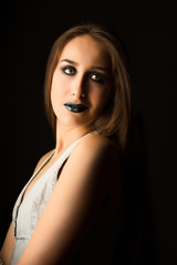 Charming young model with perfect skin and creative metallic green makeup. Closeup portrait at studio on a dark background