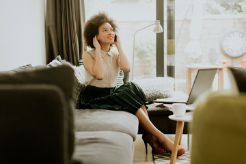 African american woman using mobile phone in the room
