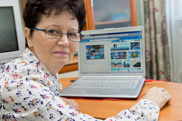 Positive senior woman sitting at the notebook at home and looking pictures on travel sites