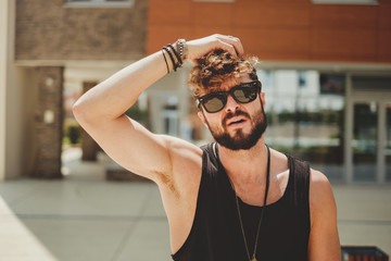 Hipster man holding hair and thinking