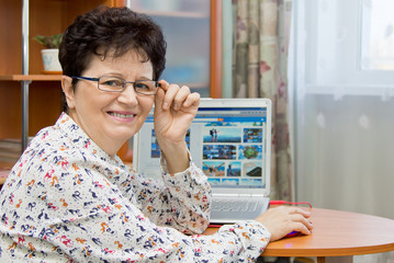 Happy smiling senior woman sitting at the notebook at home and looking pictures on travel sites