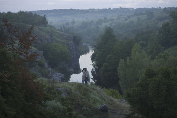Caucasian couple standing on hill above river