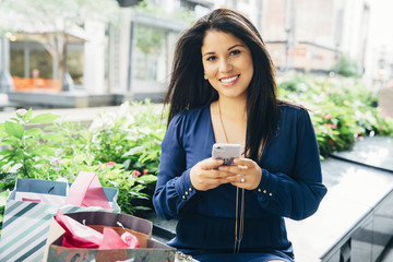 Portrait of smiling Hispanic woman with shopping bags texting on cell phone