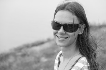 Woman 25-30 in sunglasses stands on the hill. Closeup portrait. BW.