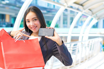Happy business woman holding shopping red bag and show mobile smartphone in modern city. Concept of online shopping, presentation technology and business customer.