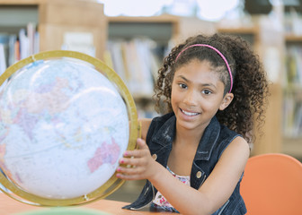Smiling mixed race girl posing with globe in library