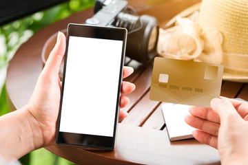 Woman hand holding a credit card and a smart phone in the coffee shop for a shopping on-line concept.