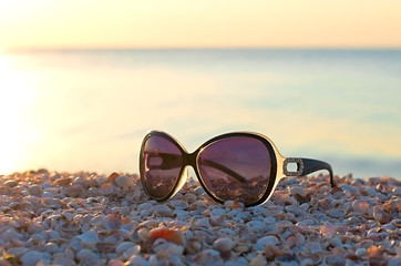 Fotomurais - sunglasses for women on the beach of seashells, against the background of the sea and the sun