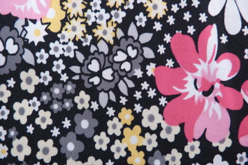 motley silk fabric with large flowers abstract drawing black franc pink flowers closeup background for design vintage bright pattern