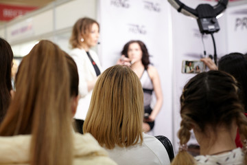 Rear view from the back of a group of girls students at a presentation, training on make-up.