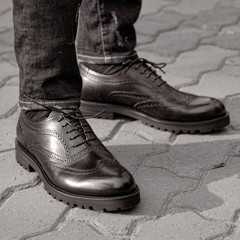 A man in the street wearing black shoes