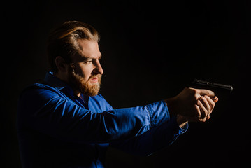 Handsome man in a blue shirt standing against black background. Security man aiming pistol.