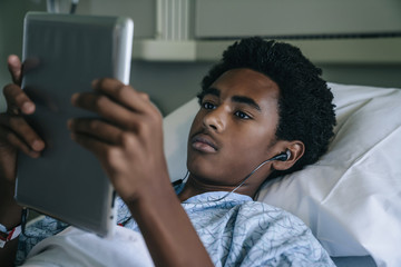 Black boy laying in hospital bed listening to digital tablet