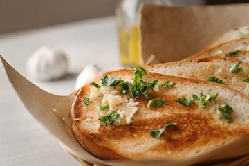Delicious homemade garlic bread on table, closeup