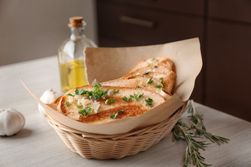 Basket with delicious homemade garlic bread on table