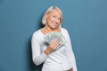 Happy mature woman with lot of dollar banknotes on color background