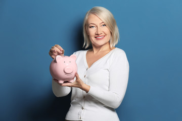 Happy mature woman putting coin into piggy bank on color background