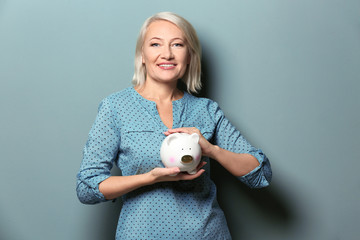 Happy mature woman with piggy bank on color background