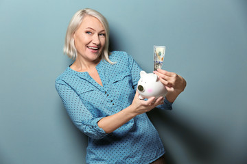 Happy mature woman with dollar banknote and piggy bank on color background