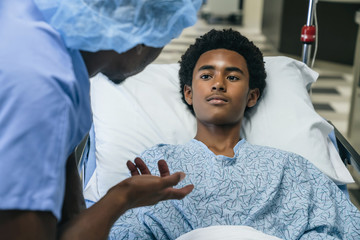 Black doctor talking to boy in hospital bed