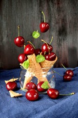 Cherries falling into waffle cones on dark wooden background