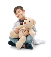 Cute little boy in doctor uniform playing with toy bear on white background