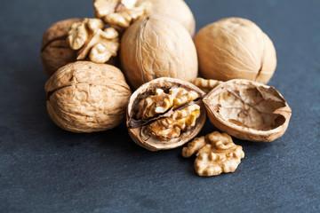 Ripe walnuts harvest on black stone background, macro view selective focus