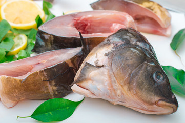 Raw fish with greens on a white cutting board