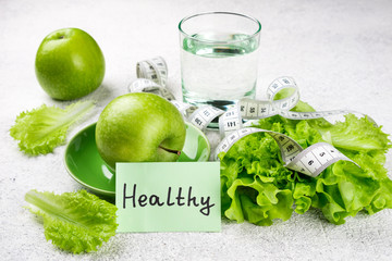 Healthy eating. Green apple, lettuce salad, glass of water, measuring tape. Dieting, slimming, weight loss and meal planning concept