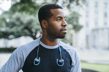 Serious Black man with earbuds looking away