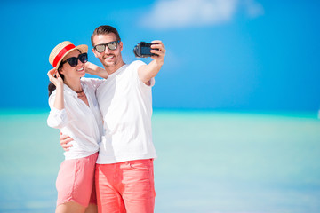 Couple taking selfie on the beach. Tourists people taking travel photos on summer holidays.