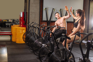 concentrated couple riding on stationary bicycles during intensive workout