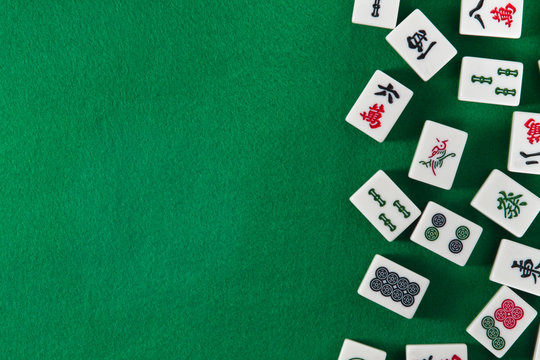 White-green tiles for mahjong on on green cloth background. Emty space on the left
