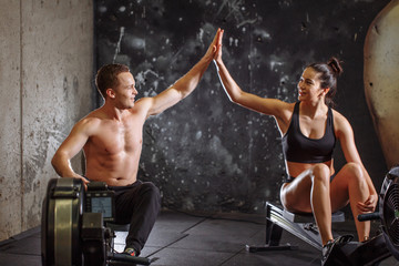 man and woman giving high-five while doing exercises with rowing machine at gym