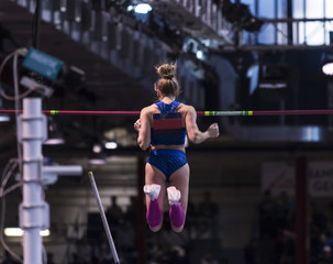 Female pole vaulter clearing the bar