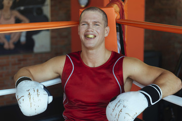 Portrait of Caucasian boxer sitting in corner of boxing ring