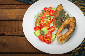 Grilled fish steak with vegetables on plate: tomatoes, microgran, cucumber, tasty and healthy dinner. Wooden rustic background. Top view