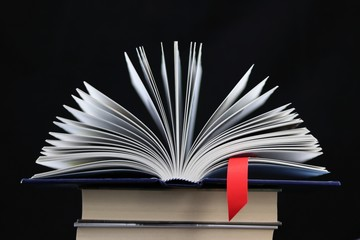An open book with a red bookmarrk