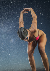 Water splashing on Caucasian swimmer stretching arms