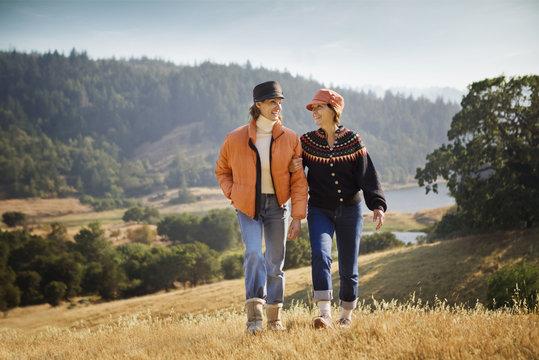 Women walking arm in arm near field