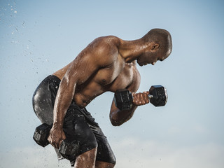 Water splashing on Black man lifting weights