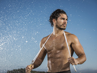 Water splashing on Hispanic man holding jump rope