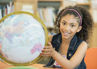Portrait of smiling mixed race girl holding globe
