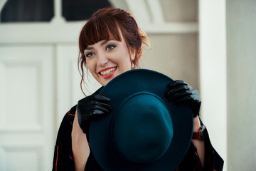 Close-up fashion woman portrait holds hat. Young trendy female caucasian smiling. Girl tourist wearing a hat.