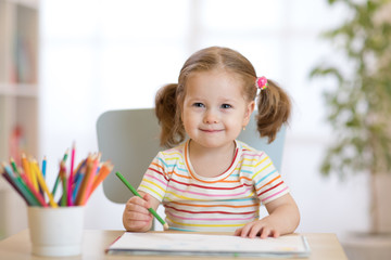 Cute happy little child girl drawing with pencils in daycare center