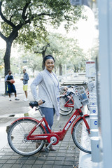 Black woman posing with rental bicycle